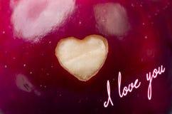 Κείμενο που γράφεται σ' αγαπώ στο φρέσκο κόκκινο μήλο με ένα διαμορφωμένο καρδιά γ Στοκ εικόνα με δικαίωμα ελεύθερης χρήσης