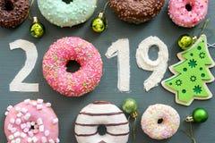 Κείμενο 2019 που περιβάλλεται από τα πολύχρωμα donuts και τα παιχνίδια Χριστουγέννων στοκ φωτογραφίες