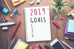 κείμενο 2019 στόχων στο σημειωματάριο με τα εξαρτήματα γραφείων περιοδεύστε τα επιχειρησιακά κινούμενα σχέδια λεπτομερή αισθάνετα στοκ φωτογραφία με δικαίωμα ελεύθερης χρήσης