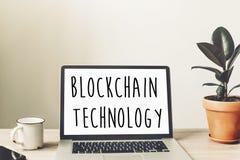 Κείμενο τεχνολογίας Blockchain στην οθόνη lap-top στα ξύλινα WI υπολογιστών γραφείου Στοκ Φωτογραφίες
