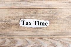 Κείμενο φορολογικού χρόνου σε χαρτί Φορολογικός χρόνος λέξης σε σχισμένο χαρτί σωστό μόνιμο κείμενο υπολοίπου εικόνας ειδωλίων έν Στοκ Φωτογραφία