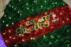 Κείμενο χαιρετισμών εποχών που διακοσμείται στην πράσινη κόκκινη σφαίρα δέντρων διακοσμήσεων Χριστουγέννων Στοκ Εικόνες