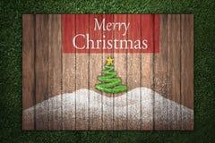 Κείμενο Χαρούμενα Χριστούγεννας στον ξύλινο πίνακα στη χλόη Στοκ Εικόνα
