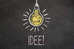 """Κείμενο """"Idee """"κιμωλίας και lightbulb στον πίνακα κιμωλίας Μετάφραση: """"Ιδέα """" διανυσματική απεικόνιση"""