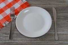 Κενά άσπρα στρογγυλά πιάτο, μαχαίρι, δίκρανο και τραπεζομάντιλο στο ξύλινο τ Στοκ Φωτογραφία