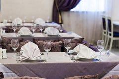 Κενά γυαλιά και πιάτα που τίθενται σε ένα εσωτερικό νέο εστιατόριο πολυτέλειας με τους καλυμμένους πίνακες Στοκ φωτογραφίες με δικαίωμα ελεύθερης χρήσης