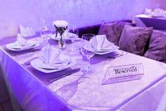 Κενά γυαλιά και πιάτα που τίθενται σε ένα εσωτερικό νέο εστιατόριο πολυτέλειας με τους καλυμμένους πίνακες Στοκ Εικόνες