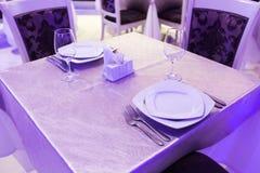Κενά γυαλιά και πιάτα που τίθενται σε ένα εσωτερικό νέο εστιατόριο πολυτέλειας με τους καλυμμένους πίνακες Στοκ φωτογραφία με δικαίωμα ελεύθερης χρήσης