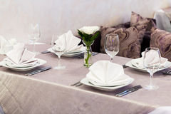 Κενά γυαλιά και πιάτα που τίθενται σε ένα εσωτερικό νέο εστιατόριο πολυτέλειας με τους καλυμμένους πίνακες Στοκ Φωτογραφίες