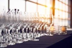 Κενά γυαλιά κρασιού στη σειρά στο φραγμό πρίν εξισώνει το κόμμα και το γεύμα Στοκ Εικόνες