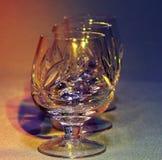 Κενά γυαλιά κρυστάλλου στο χρωματισμένο ελαφρύ τονισμό Στοκ Φωτογραφίες