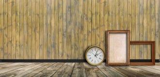 Κενά εκλεκτής ποιότητας πλαίσια και ρολόι ενάντια σε έναν ξύλινο τοίχο στοκ εικόνες