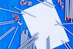 Κενά μολύβια κομματιών χαρτί και χρώματος στο μπλε ξύλινο υπόβαθρο Στοκ Εικόνα