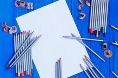 Κενά μολύβια κομματιών χαρτί και χρώματος στο μπλε ξύλινο υπόβαθρο Στοκ Φωτογραφία