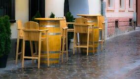 Κενά ξύλινα καρέκλες και επιτραπέζια βαρέλια στην οδό τη βροχερή ημέρα στοκ εικόνες με δικαίωμα ελεύθερης χρήσης