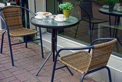 Κενά πιάτα και ένα δοχείο με εγκαταστάσεις σε έναν πίνακα με δύο καρέκλες Στοκ εικόνα με δικαίωμα ελεύθερης χρήσης