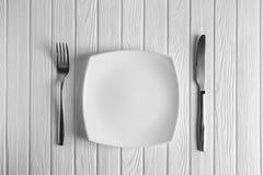 Κενά πιάτο, δίκρανο και μαχαίρι στο ξύλινο υπόβαθρο Στοκ εικόνες με δικαίωμα ελεύθερης χρήσης
