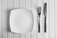 Κενά πιάτο, δίκρανο και μαχαίρι στο ξύλινο υπόβαθρο Στοκ Εικόνα
