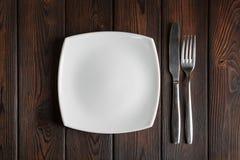 Κενά πιάτο, δίκρανο και μαχαίρι στο σκοτεινό ξύλινο υπόβαθρο Στοκ Φωτογραφία