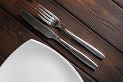 Κενά πιάτο, δίκρανο και μαχαίρι στο σκοτεινό ξύλινο υπόβαθρο Στοκ φωτογραφίες με δικαίωμα ελεύθερης χρήσης