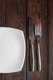 Κενά πιάτο, δίκρανο και μαχαίρι στο σκοτεινό ξύλινο υπόβαθρο Στοκ φωτογραφία με δικαίωμα ελεύθερης χρήσης