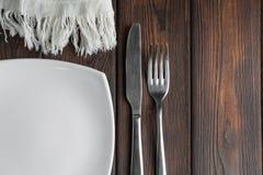 Κενά πιάτο, δίκρανο και μαχαίρι στο σκοτεινό ξύλινο υπόβαθρο Στοκ εικόνα με δικαίωμα ελεύθερης χρήσης