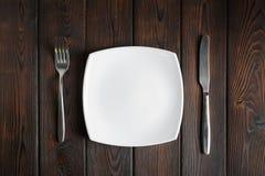 Κενά πιάτο, δίκρανο και μαχαίρι στο σκοτεινό ξύλινο υπόβαθρο Στοκ Φωτογραφίες