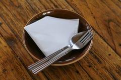 Κενά πιάτο και δίκρανο, κουτάλι σε ξύλινο Στοκ Φωτογραφίες