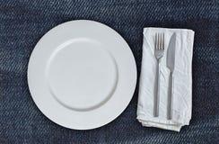 Κενά πιάτο και μαχαιροπήρουνα στο ύφασμα τζιν Στοκ Εικόνες