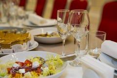 Κενά ποτήρια της σαμπάνιας και του κρασιού με τα νόστιμα πρόχειρα φαγητά στον πίνακα συμποσίου στοκ εικόνες
