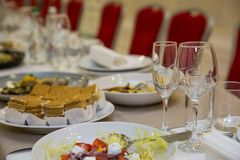 Κενά ποτήρια της σαμπάνιας και του κρασιού με τα νόστιμα πρόχειρα φαγητά στον πίνακα συμποσίου στοκ εικόνες με δικαίωμα ελεύθερης χρήσης