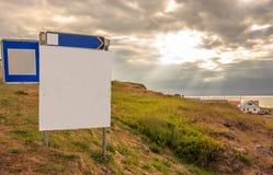 Κενά σημάδια οδών στην ηλιοφάνεια ανατολής ουρανού λυκόφατος μέσω του σύννεφου με το υπόβαθρο θάλασσας, έτοιμο για τη διαφήμιση στοκ εικόνες