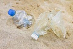 Κενά τσαλακωμένα πλαστικά μπουκάλια του νερού που εγκαταλείπονται στην παραλία Στοκ εικόνα με δικαίωμα ελεύθερης χρήσης