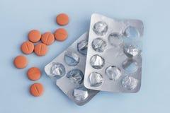 Κενά φουσκάλα και χάπια στο μπλε υπόβαθρο, ιατρική έννοια στοκ φωτογραφία