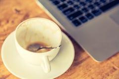 Κενά φλυτζάνι και lap-top καφέ στον παλαιό ξύλινο πίνακα Στοκ Εικόνες