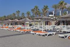 Κενά deckchairs με τα στρώματα και τις πετσέτες και ομπρέλες με το α στοκ φωτογραφία με δικαίωμα ελεύθερης χρήσης