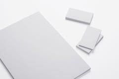 Κενές A4 έγγραφο και επαγγελματικές κάρτες τυπωμένων υλών στο λευκό απεικόνιση αποθεμάτων