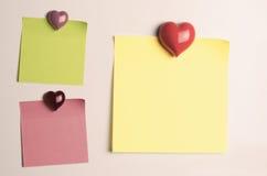 Κενές κολλώδεις σημειώσεις υπενθυμίσεων με διαμορφωμένους τους καρδιά μαγνήτες ψυγείων στοκ εικόνα