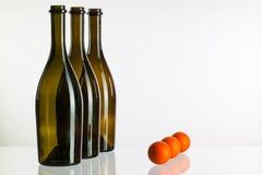 Κενές μπουκάλια κρασιού και σφαίρες γκολφ σε ένα γραφείο γυαλιού Στοκ Εικόνα