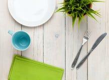 Κενές πιάτο, φλυτζάνι και ασημικές πέρα από το άσπρο ξύλινο επιτραπέζιο backgrou στοκ εικόνες με δικαίωμα ελεύθερης χρήσης