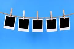 Κενές στιγμιαίες τυπωμένες ύλες φωτογραφιών σε μια γραμμή πλύσης Στοκ Φωτογραφίες