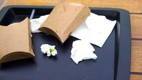 Κενές συσκευασίες γρήγορου φαγητού και τσαλακωμένος ιστός στον πλαστικό δίσκο, καφές αυτοεξυπηρετήσεων στοκ εικόνα