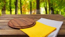 Κενές τέμνουσες κίτρινες γκρίζες πετσέτες γραφείων στον ξύλινο πίνακα στο θολωμένο υπόβαθρο πάρκων στοκ φωτογραφίες