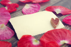Κενή άσπρη αρχαία φωτογραφία με τη διακοσμητική καρδιά σε μια ξύλινη επιφάνεια στα διεσπαρμένα ρόδινα πέταλα παπαρουνών Στοκ φωτογραφία με δικαίωμα ελεύθερης χρήσης