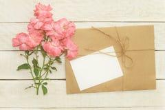 Κενή άσπρη ευχετήρια κάρτα με τη ρόδινη ροδαλή ανθοδέσμη λουλουδιών και env Στοκ Εικόνες