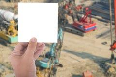 Κενή άσπρη κάρτα λαβής χεριών πέρα από το εργοτάξιο οικοδομής θαμπάδων με το trac Στοκ φωτογραφία με δικαίωμα ελεύθερης χρήσης