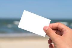 Κενή άσπρη κάρτα εκμετάλλευσης χεριών ατόμων Στοκ Εικόνες