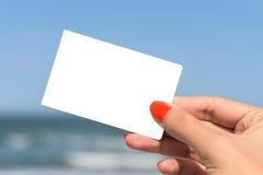 Κενή άσπρη κάρτα εκμετάλλευσης χεριών κοριτσιών Στοκ Εικόνες