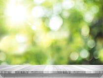 Κενή άσπρη ξύλινη επιτραπέζια κορυφή σανίδων με το πράσινο δέντρο θαμπάδων bokeh πίσω Στοκ Εικόνα