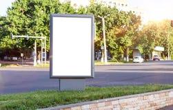 Κενή άσπρη χλεύη επάνω του κάθετου ελαφριού κιβωτίου σε μια στάση λεωφορείου στον όμορφο καιρό και την ηλιοφάνεια Στοκ φωτογραφία με δικαίωμα ελεύθερης χρήσης